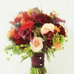 Seasonal wedding bouquet with burgundy dahlia, sunflowers, peach garden roses, calla lilies and a lot of textures. Burgundy orange peach and green bridal bouquet
