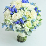 White, ivory and blue wedding bouquet. White Ivory and blue wedding bouquet. Ivory roses and spray roses, ranunculus and freesia, muskary and nigella, orchids, dusty miller gathered into a white ivory and blue bridal bouquet.