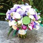 with ivory roses, calla lilies, blue delphinium, lisi and a lot of textures. Blue purple ivory green bridal bouquet peacock feathers