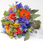Bridesmaid's bouquet of blue and orange wild flowers.