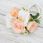 Wrist corsage of white orchids and peach spray roses