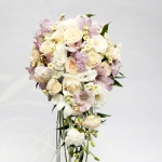 Cascading bridal bouquet with purple alstroemeria and delicate creamy roses