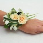 Lady's wrist corsage of white orchids and ivory spray roses