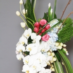 Funeral flowers Standing easel of white irises and tulips, white orchids and pink roses, blue hydrangea. Spray has a contemporary shape.