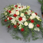 Full casket spray of white and red flowers. Casket spray of white lilies, white roses and white football mums, red roses