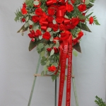 Funeral flowers Standing easel of red roses and red spray roses, red carnations. Spray has a classic oval shape.