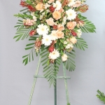 Funeral flowers Standing easel of peach roses, white gerberas, white alstroemeria and leucodendron. Spray has a classic oval shape.
