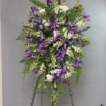 Funeral flowers Standing easel of purple irises, white snaps and purple statice. Spray has a classic oval shape.