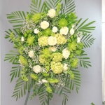 Funeral flowers Standing easel of green spider mums, white roses, green hydrangea and green chysanthemum. Spray has a classic oval shape.