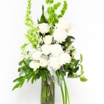 Vase arrangement of long lasting white flowers as white roses, lilies, football mums, carnations, snapdragon finished with soft grey foliage and greenery