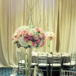 White-pink-gray tall wedding centerpiece of pink roses, white roses, white hydrangea, pink dahlia,  amaryllis as naked lady, gray dusty miller. Recepition centerpiece
