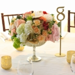 Short Centerpiece in mercury compote vase White, peach, blush, and cream sophisticated blooms such as peonies, garden roses, lisianthus and ranunculus, viburnum, partnered with touches of gray dusty miller and gold eucalyptus foliage.