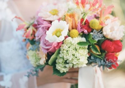 Lush bridal bouquet of spring flowers, white poppy, orange parot tulips, red garden roses, gorgeous gloriosa, green hydrangea, pink nerine lily, yellow craspedia, pink roses, and kumquats