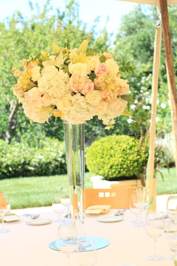 Tall centerpiece of white, peach and light yellow, and pink flowers for wedding reception