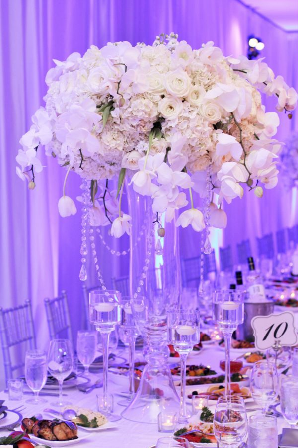 Tall centerpiece of white hydrangea, orchids, roses and tulips for wedding reception