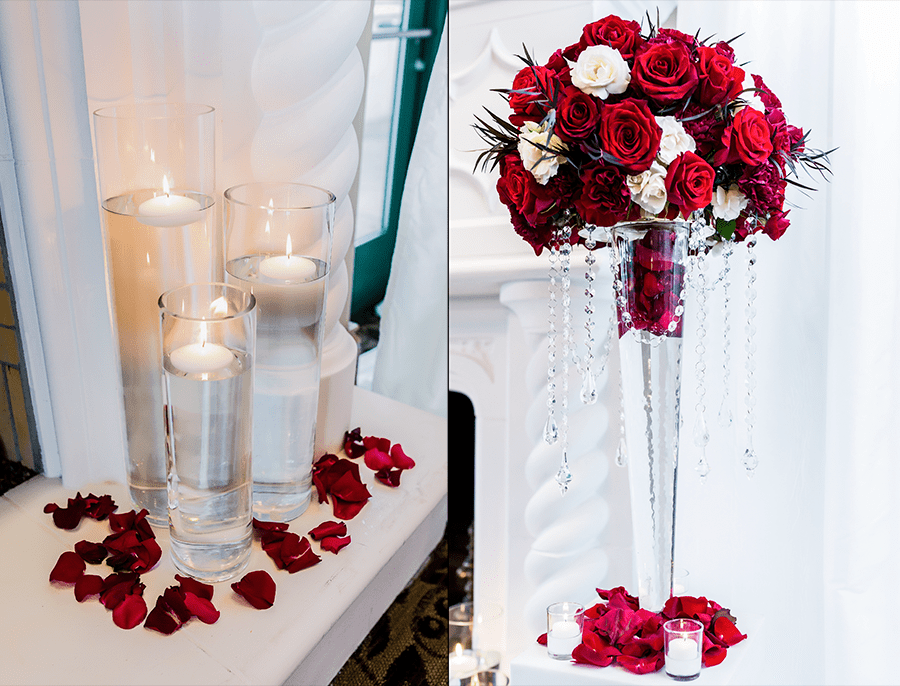 Red roses and ivory spray roses tall floral design onto a vase with hanging crystals