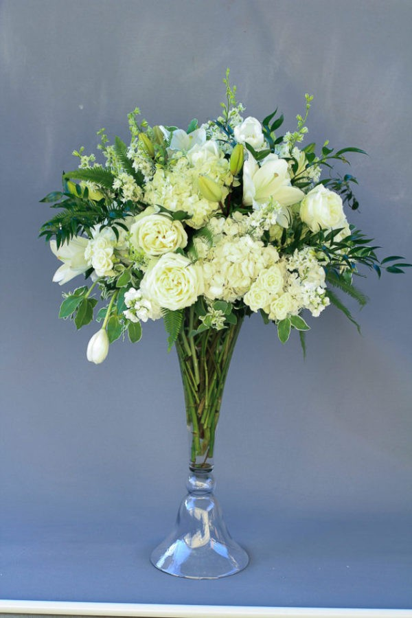 Tall centerpiece of white, peach and green flowers for wedding reception