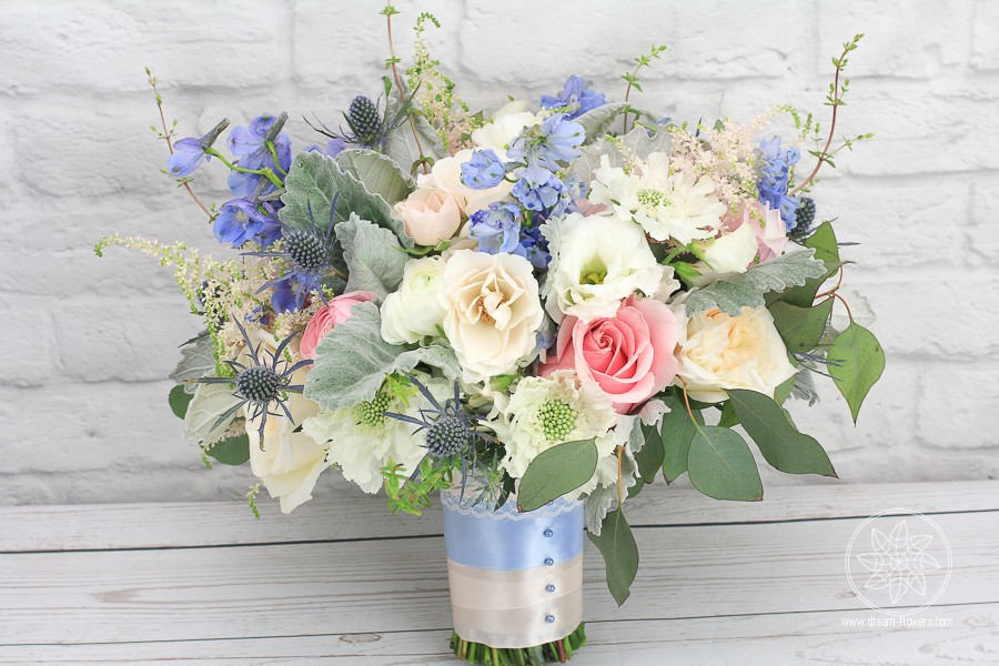 Bridal Bouquet of cream garden roses, pink roses, blue delphinuim, cream spray roses, blue hydrangea, blue thistle, white lisianthus, white scabiosa, pink astilbe and dusty miller, complimented by eucalyptus and thyme.